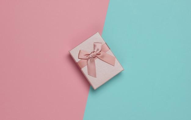 Pudełko z kokardą na pastelowym tle niebiesko-różowym. kompozycja na boże narodzenie, urodziny lub wesele. widok z góry