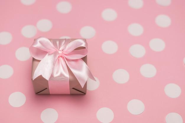 Pudełko z kokardą z różowej wstążki na pastelowym różowym stole z białymi konfetti.