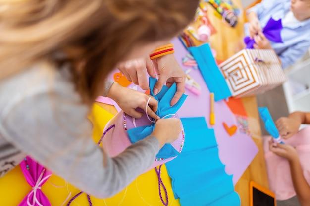Pudełko z kokardkami. ciemnowłosa dziewczyna i pomocna nauczycielka dekorują pudełko na prezenty papierowymi kokardkami