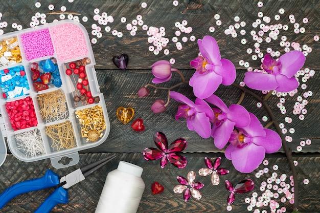 Pudełko z koralikami, szpulą nici, szczypcami i szklanymi sercami do tworzenia ręcznie robionej biżuterii na starym drewnianym tle. ręcznie robione akcesoria. kwiaty orchidei