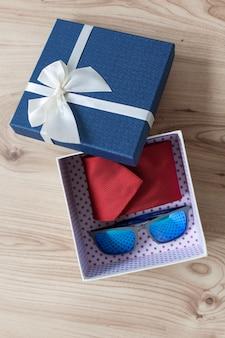 Pudełko z krawatem i okulary słoneczne