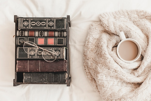 Pudełko z książkami blisko gorącego napoju w szkockiej kraty