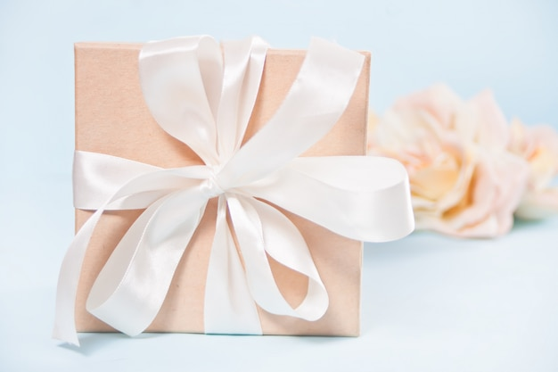 Pudełko z kwiatami beżowe róże na tle.