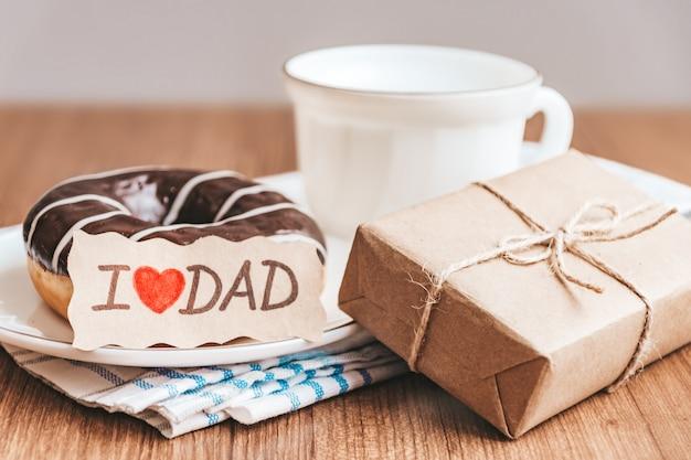 Pudełko z metką, filiżanką kawy lub herbaty i pączka czekolady