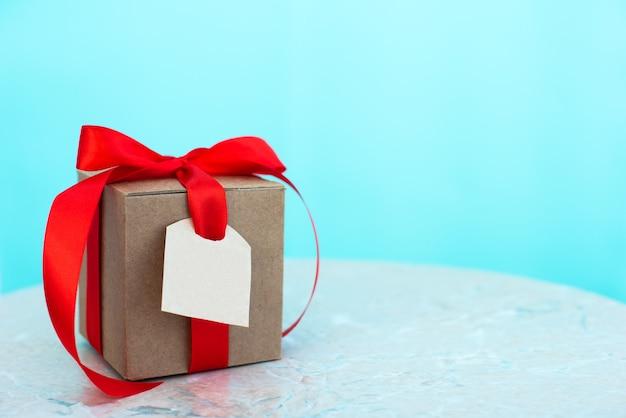 Pudełko z metką i czerwoną kokardą, na niebieskim tle. szczęśliwy dzień ojca, wakacje, zaproszenie, urodziny, koncepcja walentynki. miejsce na tekst