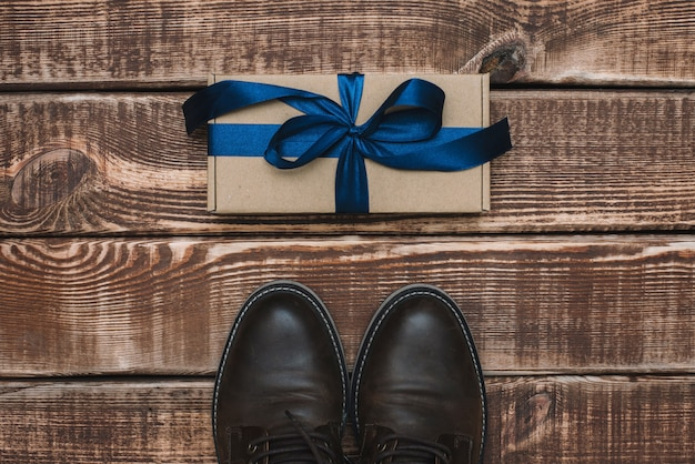 Pudełko z niebieską wstążką i męskie skórzane buty na drewnianym stole. dzień ojca. prezent dla mężczyzny. leżał płasko.