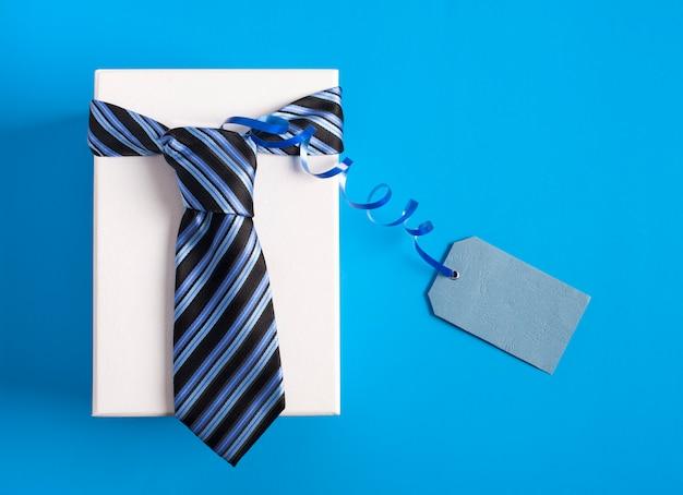 Pudełko z niebieskim krawatem w paski. szczęśliwy dzień ojca pomysł, znak, symbol. tło wakacje