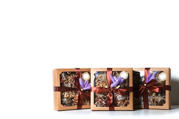 Pudełko z orzechami na białym tle izolacyjne na wakacje. prezenty zapakowane w pudełko ozdobione bordową wstążką i fioletowymi piórami. prezenty na boże narodzenie, rocznicę, urodziny. skopiuj miejsce