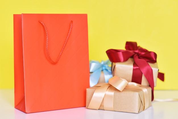 Pudełko z papierową torbą na zakupy ribbonnd na żółtym tle