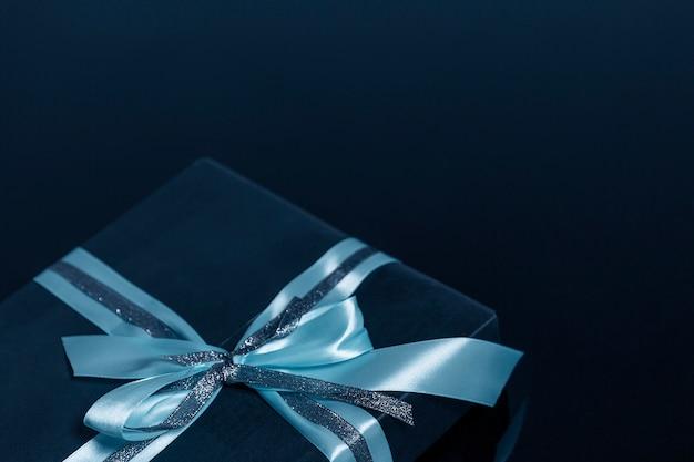 Pudełko z piękną kokardą na niebieskim tle. zbliżenie. miejsce na tekst.
