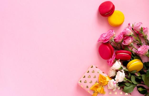 Pudełko z piękną złotą wstążką, ciastem macaron i różami. koncepcja walentynki.