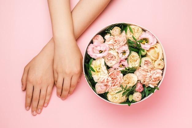 Pudełko z pięknymi kwiatami obok rąk womans na czarnym tle z miejsca na kopię. piękno