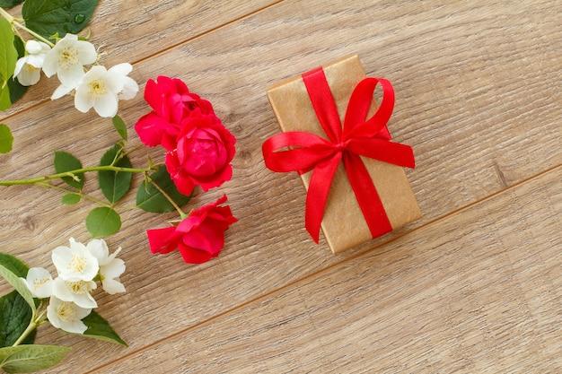Pudełko z pięknymi kwiatami róży i jaśminu na drewnianym tle. koncepcja dawania prezentu na święta. widok z góry.