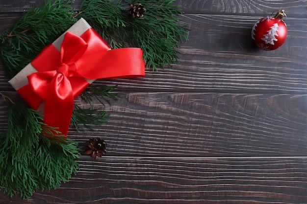 Pudełko z prezentem i czerwoną kokardą wstążką na drewnianym tle.