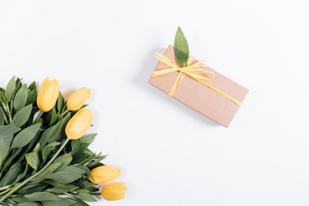 Pudełko z prezentem i żółtymi tulipanami na białym tle