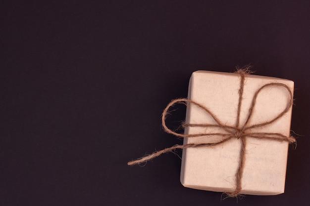 Pudełko z prezentem wykonane z papieru kraft przewiązanego konopną liną. ciemne tło z czerwonym odcieniem. skopiuj miejsce.