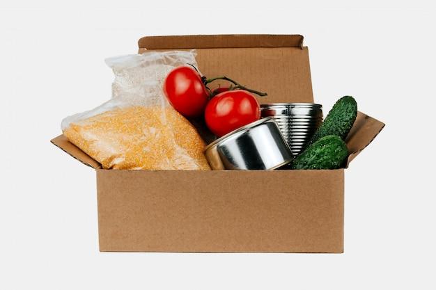 Pudełko z produktami. warzywa, zboża i konserwy w kartonowym pudełku na białym tle.