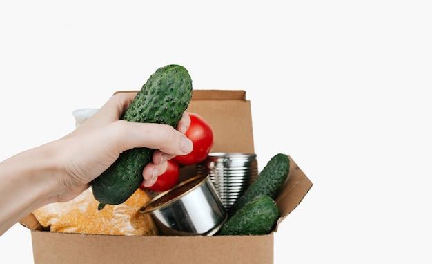 Pudełko z produktami. warzywa, zboża i konserwy w tekturowym pudełku. ogórek w dłoni.