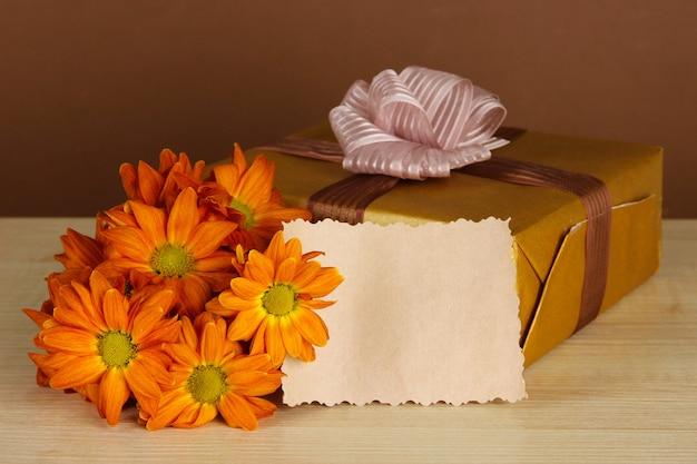 Pudełko z pustą etykietą i kwiatami na stole na brązowym tle
