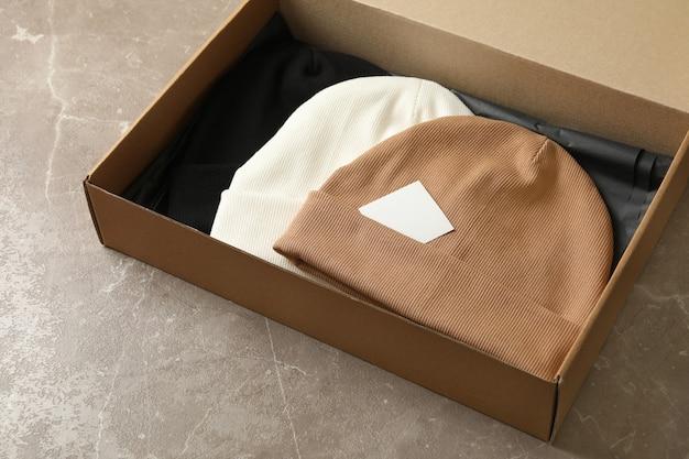 Pudełko z różnymi czapkami na szarym stole