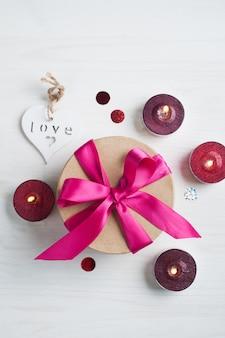 Pudełko z różową kokardką i zapalonymi świecami