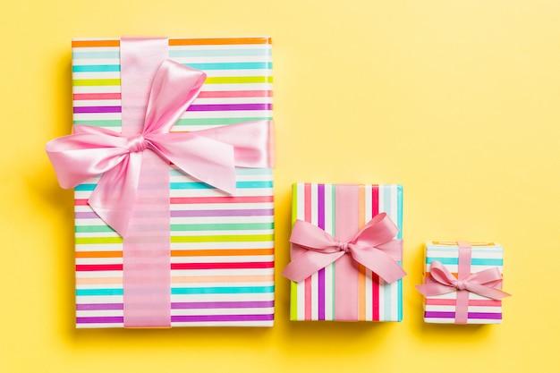 Pudełko z różową kokardką na boże narodzenie na żółtym tle
