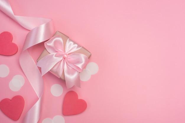 Pudełko z różową kokardką na pastelowym różowym stole z białymi konfetti i sercami