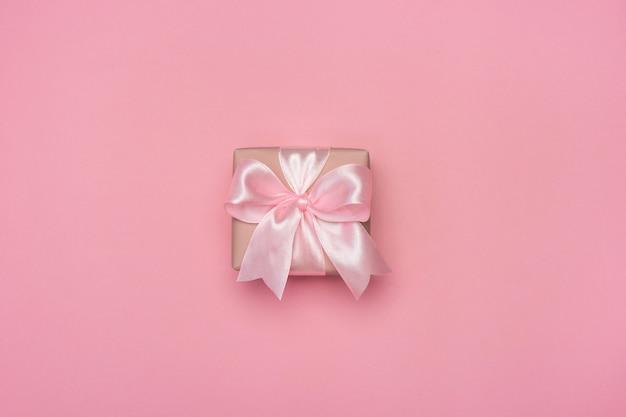 Pudełko z różową wstążką na pastelowym różowym stole.