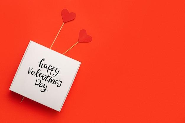 Pudełko z tekstem miłość i serca na patyku na czerwonym tle. kompozycja walentynki. transparent. widok płaski, widok z góry.