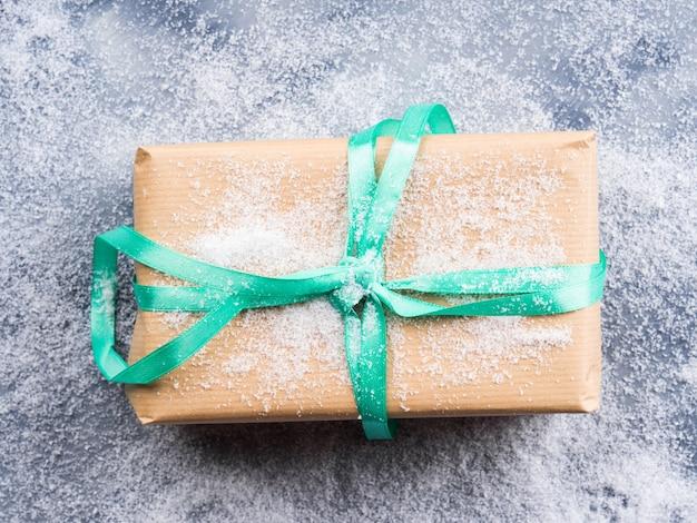 Pudełko z zieloną wstążką i śniegiem