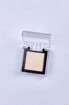 Pudełko z złote cienie do powiek na białym tle. kobiece kosmetyki dekoracyjne.