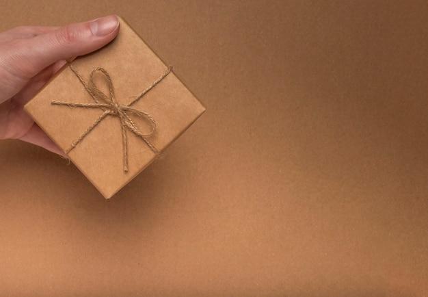 Pudełko zapakowane w papier rzemieślniczy z kokardą jutową w kobiecej dłoni na tekturze eco kraft.