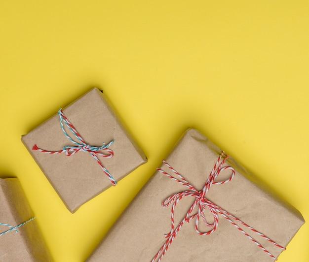 Pudełko zawinięte w brązowy papier i przewiązane liną, prezent na żółtym tle, widok z góry, miejsce na kopię