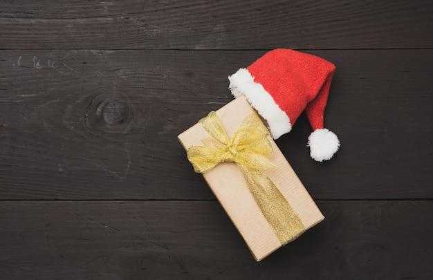 Pudełko zawinięte w brązowy papier pakowy i czerwoną czapkę, prezent na drewnianym tle, widok z góry