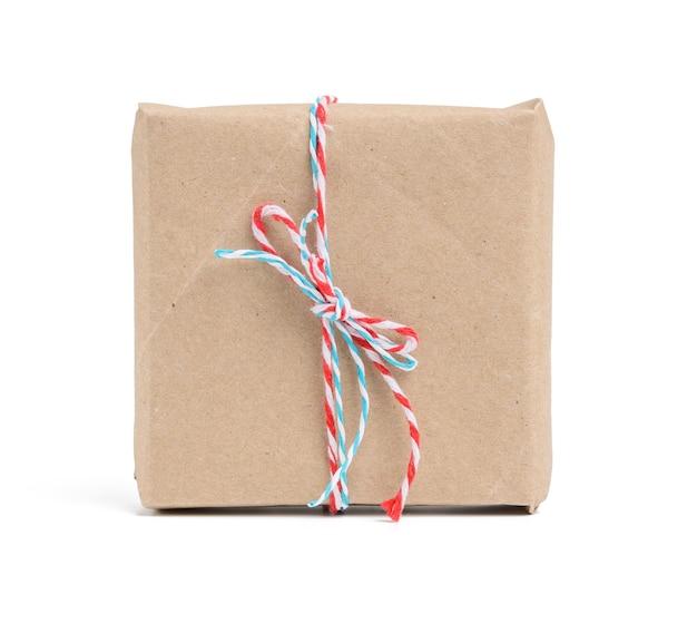 Pudełko zawinięte w brązowy papier pakowy i przewiązane czerwoną liną, prezent na białym tle