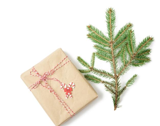 Pudełko zawinięte w brązowy papier pakowy i przewiązane liną, prezent na białym tle, widok z góry
