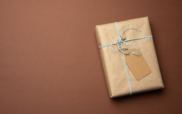 Pudełko zawinięte w brązowy papier pakowy i przewiązane liną, prezent na brązowym tle, widok z góry
