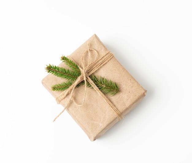 Pudełko zawinięte w brązowy papier pakowy i przewiązane sznurem, prezent na białym tle