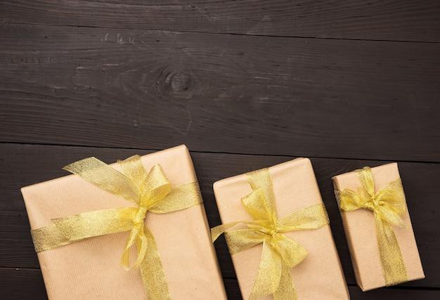 Pudełko zawinięte w brązowy papier przewiązane złotą wstążką z kokardką, prezent na drewnianym tle, widok z góry
