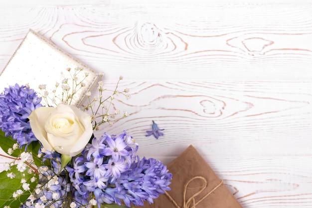 Pudełko zawinięte w papier i niebieskie hiacyntowe kwiaty, białe róże na białym blacie