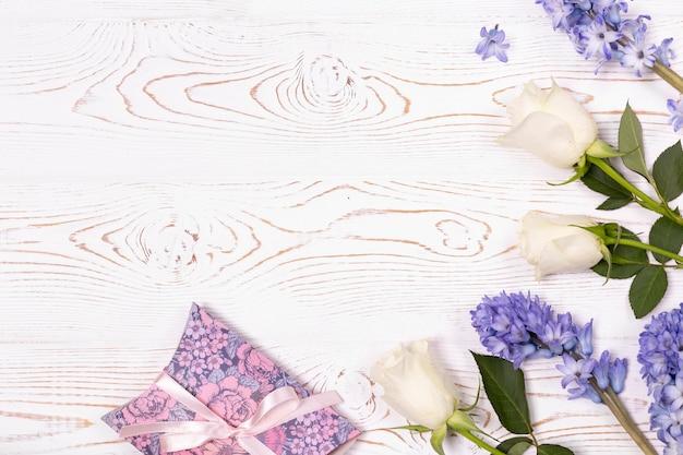 Pudełko zawinięte w papier i niebieskie kwiaty, białe róże na białym blacie
