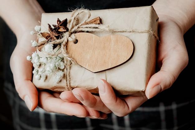 Pudełko zawinięte w papier kraft ozdobiony drewnianym sercem i białymi kwiatami w dłoniach