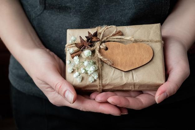 Pudełko zawinięte w papier kraft ozdobiony drewnianym sercem i białymi kwiatami w ludzkich rękach. obchody walentynek