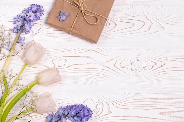 Pudełko zawinięte w papier kraftowy i niebieskie kwiaty, białe róże na białym blacie