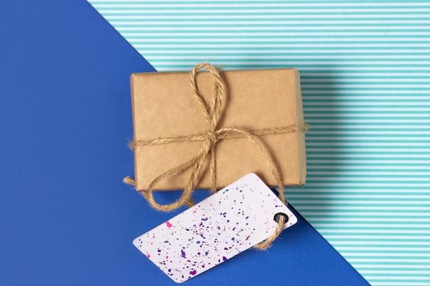 Pudełko zawinięte w papier pakowy na niebieskim tle