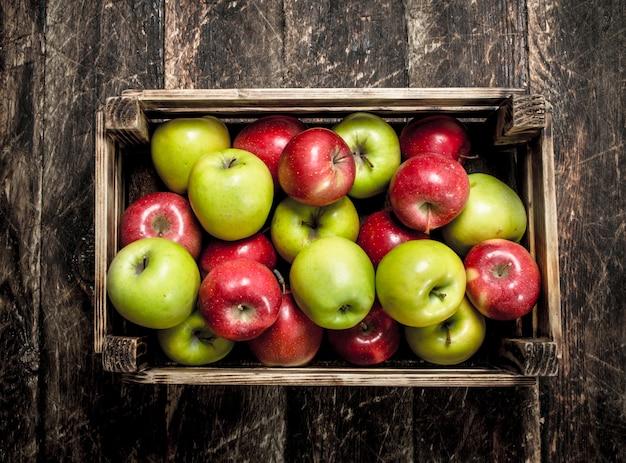 Pudełko ze świeżymi czerwonymi i zielonymi jabłkami. na drewnianym tle.