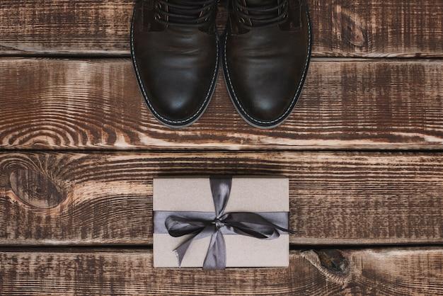 Pudełko ze wstążką i męskie skórzane buty na drewnianym stole. dzień ojca. prezent dla mężczyzny. leżał płasko.