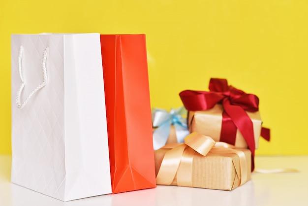 Pudełko ze wstążką i papierową torbą na zakupy na żółtym