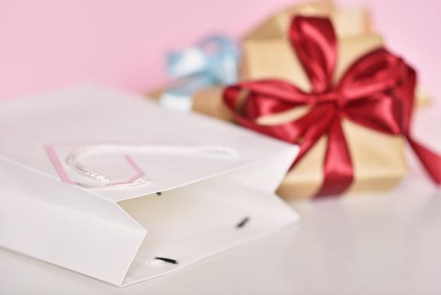Pudełko ze wstążką i papierową torbę na zakupy na różowym tle