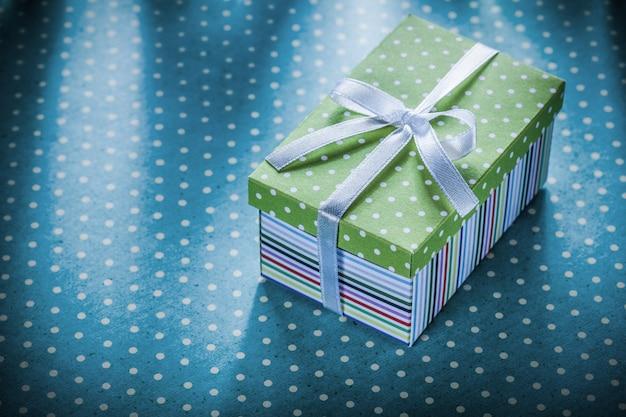 Pudełko ze wstążką na niebieskim obrusie w kropki koncepcji wakacji